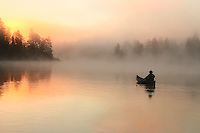 """""""Foggy Glow""""<br /> Dramatic wilderness mornings deliver mystery with the tranquil fog and promise a sunny day ahead. Paddling through a stunning scene in the Boundary Waters is a surreal and enriching experience.<br /> <br /> This photograph is from our Canoescapes Series."""