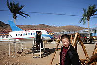 China. Jilin Province. Visitors outside an agricultural shopping centre in the town of Yanji, close to the border with North Korea. The town is part of the Korean Autonomous Prefecture in the north-east of the country. 2011