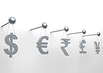 International currencies hanging on nail over white background