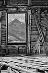 Black and white image if mountain through a window of an abandoned house.