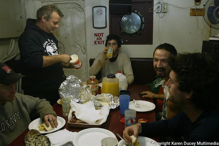 """10/20/03 crab NWS::  Steve Toomey, part owner of the F/V Exito (standing left), shares breakfast and a laugh with the crew during a break in the galley during the Bristol Bay red king crab season.  Either Toomey, who usually takes care of cooking while fishing, or the other captain, Quinn Ferguson, will eat with the crew during meals to try and keep them as informed as possible as to what the next plan is or """"when their next 15 minutes of sleep will be."""""""
