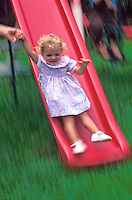 Little girl sliding down a big red slide at playground