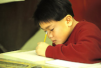 Released, Asian boy student writing in elementary school, California