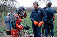 Police underwater diving unit preparing to search a river for evidence. The officers are checking their equipment before entering the water. This image may only be used to portray the subject in a positive manner..©shoutpictures.com..john@shoutpictures.com