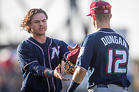 Northwest Arkansas Naturals infielder Nick Pratto (32) meets Northwest Arkansas Naturals infielder Clay Dungan (12) with his hat and glove between innings against the Wichita Wind Surge at Riverfront Stadium on July 9, 2021 in Wichita, Kansas. (William Purnell/Four Seam Images)