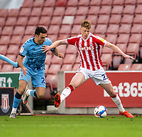 21st April 2021; Bet365 Stadium, Stoke, Staffordshire, England; English Football League Championship Football, Stoke City versus Coventry; Sam Clucas of Stoke City holds off the pressure from  Matty James of Coventry City