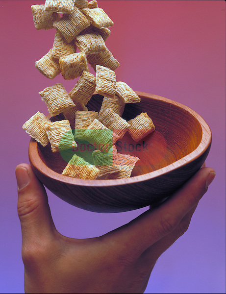 hand holding bowl with cereal being poured