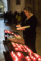 London, UK. 04.05.2015. Woman maintains the candles within the Se de Lisboa (Lisbon Cathedral). Photograph © Jane Hobson.