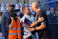 Pictured: Gareth Thomas (R) is embraced by former Wales international rugby team mate Shane Williams by the finish line. Sunday 15 September 2019<br /> Re: Ironman triathlon event in Tenby, Wales, UK.