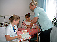 Hospital doctor and midwife attending to new born baby who is being held by her mother. The doctor and midwife are examining the infant and writing the results in her notes. This image may only be used to portray the subject in a positive manner..©shoutpictures.com..john@shoutpictures.com