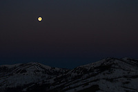 The moon begins to set over mountains in Yellowstone.