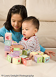 16 month old toddler boy playing with cardboard blocks moving stack tower as older sister age 8 looks on vertical