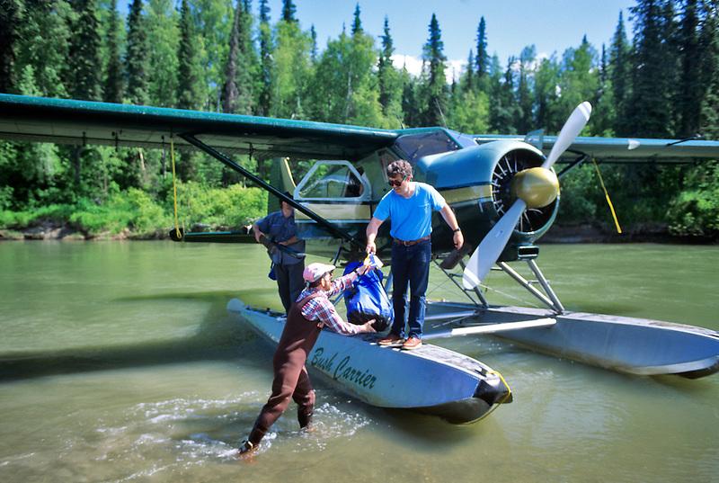 Unloading bush plane on the Talachulitna River, Alaska