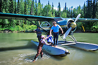 Unloading bush plane on the Talachulitna River, Alaska