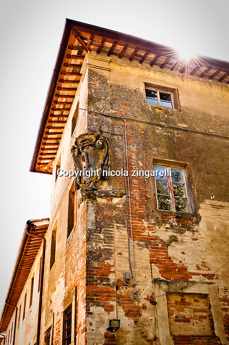 the corner and wall of an old house in villa saletta, an abandoned town in toscany, italy