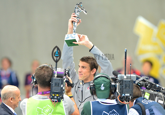 """August 04, 2012..Michael Phelps raises """"The Greatest Olympic Athlete of All Times"""" trophy, awarded to him by FINA at the Aquatics Center on day eight of 2012 Olympic Games in London, United Kingdom."""