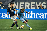 FOXBOROUGH, MA - SEPTEMBER 29: Carles Gil #22 of New England Revolution comes in to tackle Ronald Matarrita #22 of New York City FC during a game between New York City FC and New England Revolution at Gillettes Stadium on September 29, 2019 in Foxborough, Massachusetts.