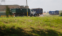 Trucks carrying waste enter and leave Tuesday, July 27, 2021, the Waste Management Ecovista Tontitown Landfill in Tontitown. Waste Management has a large scale expansion plan for the site. Check out nwaonline.com/210728Daily/ and nwadg.com/photos for a photo gallery.(NWA Democrat-Gazette/David Gottschalk)
