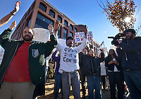 STAFF PHOTO BEN GOFF  @NWABenGoff -- 11/25/14 Nik (CQ) Robbins, left, and Jared Carter chant 'Hands up, don't shoot' before stepping in the roadway to block traffic during a protest organized by the OMNI Center for Peace, Justice & Ecology in front of the Washington County Courthouse in Fayetteville on Tuesday Nov. 25, 2014. The demonstration was in response to the decision Monday night by the St. Louis County grand jury not to indict police officer Darren Wilson, who fatally shot Michael Brown in Ferguson, Mo.
