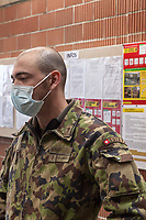 """Switzerland. Canton Ticino. Rivera. Monte Ceneri military base. Due to the spread of the coronavirus (also called Covid-19), the Federal Council has categorised the situation in the country as """"extraordinary"""". The army was called upon to provide logistical support and to offer its skills in terms of medical assistance (ambulances, field hospital, tents, nurses,..). The militia soldiers from medical troops were called by the Swiss army for the first time since World War II. Under the country's militia system, professional soldiers constitute a small part of the military and the rest are conscripts or volunteers aged 19 to 34 (in some cases up to 50).  A soldier waits to wash his hands before entering the refectory. The bald man wears a mask in front of his mouth. On the wall, the Coronavirus poster explains how to prevent from getting the disease. The measures are: Keep your distance, wash your hands thoroughly, avoid shaking hands, cough and sneeze into a tissue or the crook of your arm, stay at home if you have fever, always call ahead before going to the doctor's or the emergency department. Monte Ceneri is a mountain pass in the canton of Ticino. It connects the Magadino plain and the Vedeggio valley across the Prealps. 2.04.2020 © 2020 Didier Ruef"""