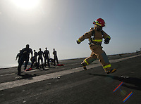 120316-N-DR144-332 ARABIAN SEA (March 16, 2012) A Sailor races to the finish line after donning a firefighting ensemble while competing in the Damage Control Olympics on the fight deck aboard the Nimitz-class aircraft carrier USS Carl Vinson (CVN 70). Carl Vinson and Carrier Air Wing (CVW) 17 are deployed to the U.S. 5th Fleet area of responsibility.  (U.S. Navy photo by Mass Communication Specialist 2nd Class James R. Evans/Released)