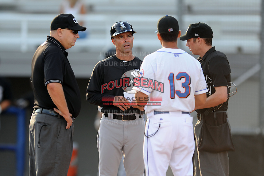 Kingsport Mets manager Jose Leger #13 and Bristol White Sox manager Mike Gellinger #73 exchange lineups and handshakes with home plate umpire Andrew Chesnut and first base umpire Andy Glenn before the game at Hunter Wright Stadium on August 15, 2013 in Kingsport, Tennessee. The White Sox won the game 4-2. (Tony Farlow/Four Seam Images)