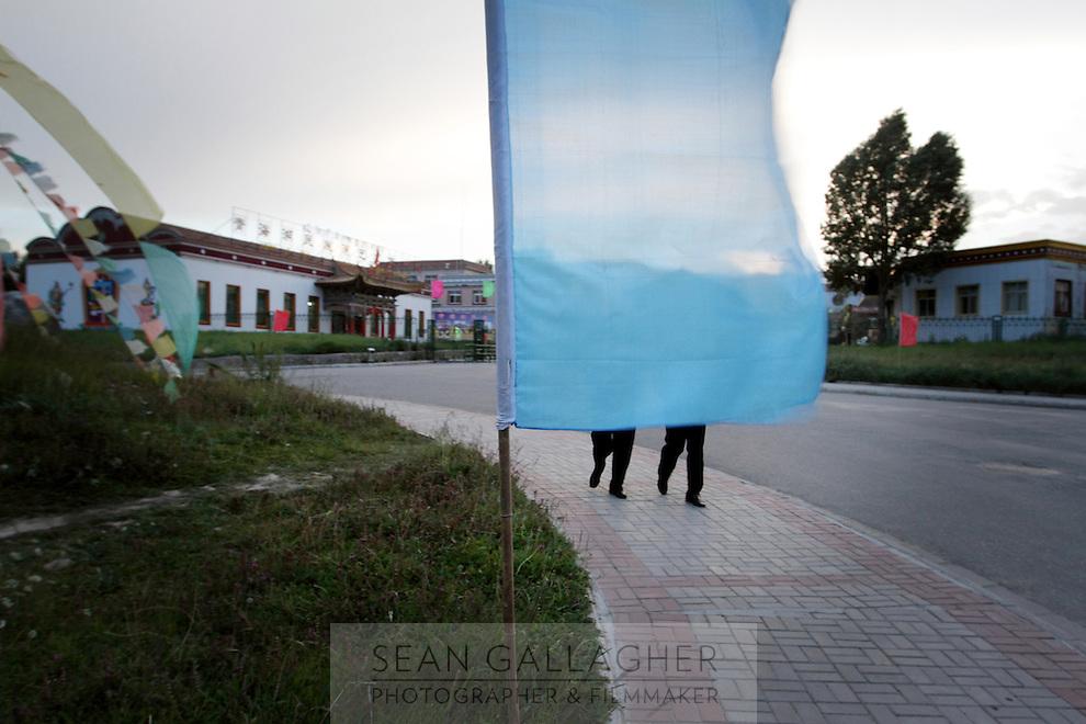 Pedestrians in a town near Qinghai Lake. Qinghai Province. China. 2010