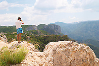 A panoramic view across the tremendously impressive Orin or Bijela Gora mountain tops close to the border to Montenegro on the road between Trebinje and Niksic. A man in colourful swimming trunks standing on a rock taking a photo. Trebinje region. Republika Srpska. Bosnia Herzegovina, Europe.
