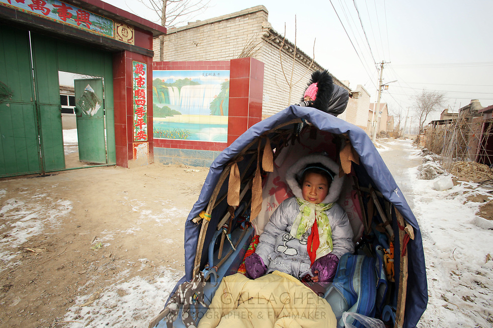 A mother and daughter ride past an elaborate and newly built gate in Dongzhuangying Village, on the southern outskirts of Beijing. Villagers have been building new extensions to their properties in-light of news that their village will be destroyed to make way for a new city airport. Villagers will be compensated more depending on the area of their homes, resulting in new buildings appearing across the village, as villagers anticipate higher amounts of compensation from local government. China. Friday 25th January, 2013.