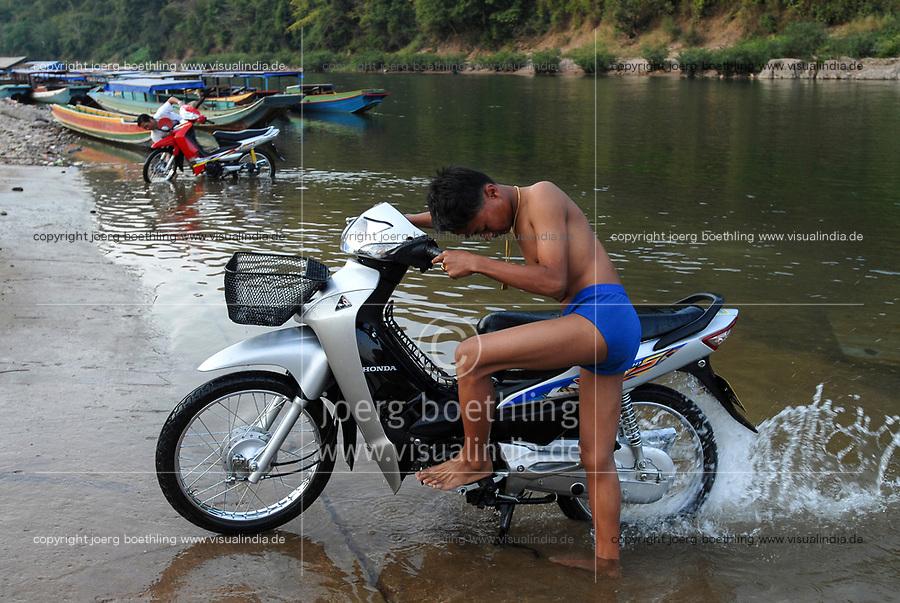 LAO PDR, Muang Khua at Nam Ou river , a branch of Mekong river , washing of Honda scooter