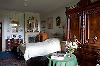 A modest bedroom hung with a pale, striped wallpaper is also home to a beautifully patinated antique armoire