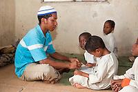 Zanzibar, Tanzania.  Imam in a Madrassa (Koranic School)  Teaching Young Boy to Read Letters of the Arabic Alphabet.