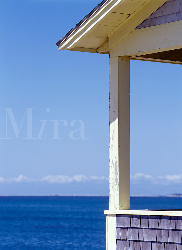 Detail of porch, expanse of water, blue sky, crisp sun. North Truro, Massachusetts on Cape Cod.