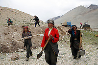 "China started building a controversial 67-mile ""paved highway fenced with undulating guardrails"" to Mount Qomolangma, known in the west as Mount Everest, to help facilitate next year's Olympic Games torch relay./// Tibetan women get back to work on the road to EBC. <br /> Tibet, China<br /> July, 2007"