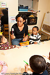 Education preschool 3-4 year olds female teacher talking to group sitting at table about how to brush teeth showing them a toothbrush vertical