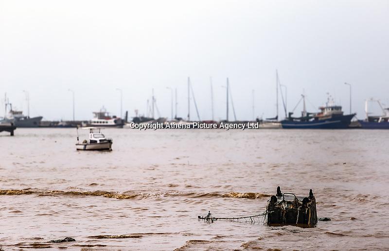 A refuse bin is seen in the water against ships in Nea Mihaniona