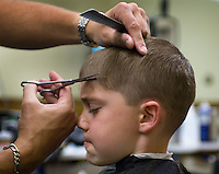 A young boy gets his hair cut by a barber in Westerville, Ohio.