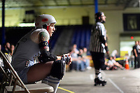 Shellby Shattered sits in the penalty box, waiting to return to a roller derby bout in Wilmington, Massachusetts. Roller derby is an American contact sport, popular with young women, which combines both athleticism and a satirical punk third-wave feminism aesthetic.