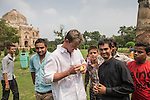 8 October 2013, New Delhi, India. Recently retired Australian cricket star Brett Lee signs an autograph for local fans before a scratch game of tennis ball cricket in front of a Mughal era tomb in the famous Lodi Gardens in New Delhi. His arrival caused great interest in the local boys in the grounds. He is in India to show off his latest fashion lines and to foster greater interest in Australian - Indian business interactions.  Picture by Graham Crouch