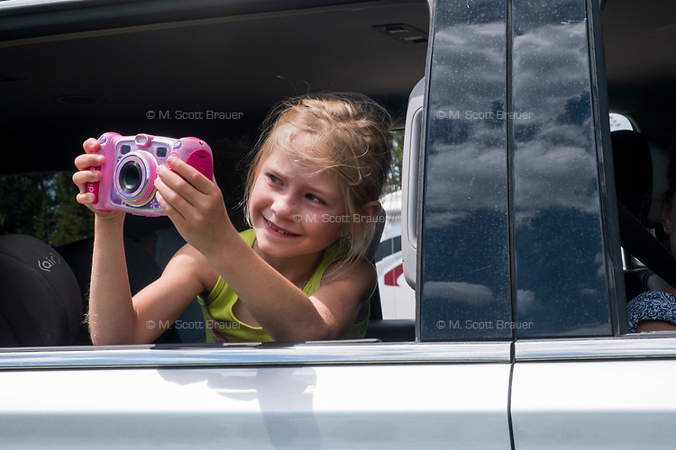 A girl from Chicago, Illinois, takes a picture from her family's car as cars stop to look at a 5-point bull elk in velvet lounging near the road near Bridge Bay on the road between West Thumb and Fishing Bridge in Yellowstone National Park, Wyoming, USA. The family said it was their first wildlife sighting of the trip.