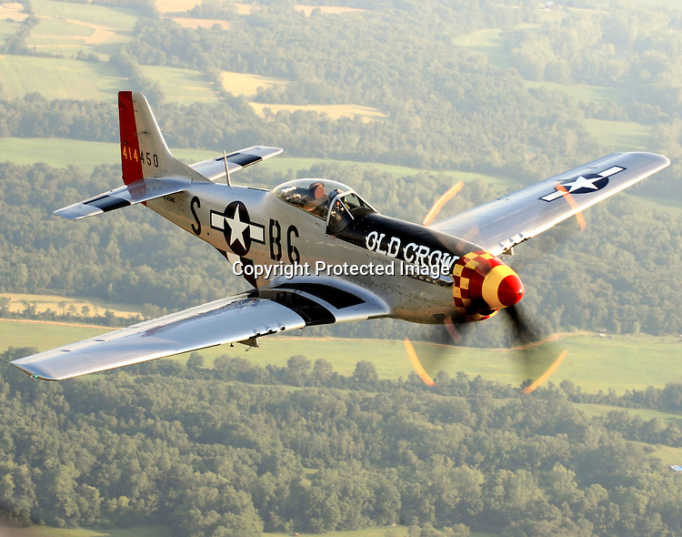 """The P51 Mustang """"Old Crow"""" flies over the Ohio countryside. The Mustang, piloted by Jim Hagedorn, was in Dayton to honor 2008 National Aviation Hall of Fame enshrinee Clarence E. """"Bud"""" Anderson, who flew the original """"Old Crow"""" on his way to becoming a triple ace during WWII."""