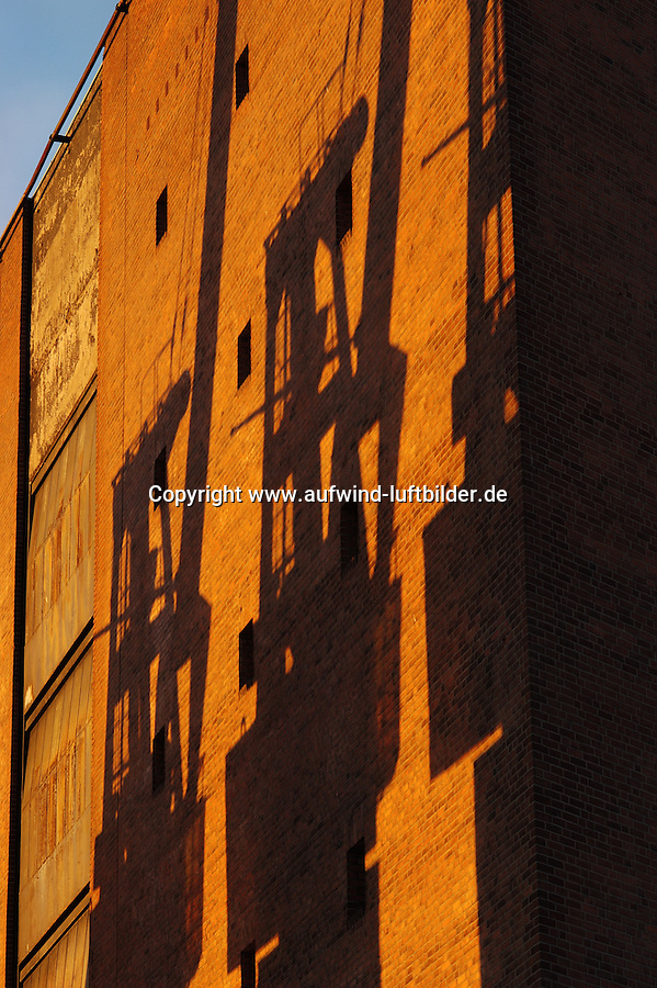 4415/Portalkran:DEUTSCHLAND, HAMBURG, 27.10.2003:Speicherstadt, Hafencity, Kaispeicher A, Schatten eines Portalkran. An der Suedseite (Elbseite) des Kaispeicher A befinden sich drei Portalkraene deren Schatten sich an der Wand des Kaispeichers abzeichnen..Ein Portalkran ueberspannt seinen Arbeitsbereich wie ein Portal. Das Portal ist eine Stahlkonstruktion ausgefuehrt in  Rahmenbauweise. Der Kran hat jeweils eine Pendelstuetze und eine starre Stuetze um die temperaturbedingte Laengenaenderung der Kranbruecke (horizontaler Teil des Portals) auszugleichen. Auf der Kranbruecke verfaehrt die Laufkatze mit dem Hubwerk. Der Kran verfaehrt meist auf frei oder im Boden versenkten Schienen in horizontaler Richtung. Die Stromzufuehrung kann ueber eine Schleppleitung oder Schleifkontakte im Boden erfolgen. Portalkrane werden meist auf Gueterumschlagplaetzen und Lagerplaetzen eingesetzt..