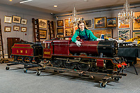 BNPS.co.uk (01202 558833)<br /> Pic: MaxWillcock/BNPS<br /> <br /> Pictured: Sale Coordinator Lulu Randall inspects a 10 1/4 inch gauge model of the London Midland and Scottish tender locomotive No 6100 'Royal Scott, built from Bassett-Lowke castings and rebuilt by William Whiteley of Newark on Trent at D. Arundel & Co 1972, in the Dreweatts Donnington Priory saleroom.<br /> <br /> A remarkably detailed, functioning model steam engine is tipped to sell for £50,000 after attracting worldwide interest from train enthusiasts.<br /> <br /> The maroon 10.25ins gauge model of the London Midland and Scottish tender locomotive No 6100 'Royal Scott' was built in Bedfordshire in 1965.<br /> <br /> It underwent a significant restoration in 1972 and is still in a 'high quality' condition half a century later.<br /> <br /> The 8ft long locomotive weighs one tonne and has a steel boiler, a coal compartment, brakes, fitted steps, handrails and railway lamps.