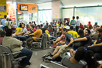 Brazil fans watch the Brazil v Mexico match on TV in the airport