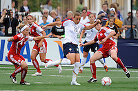 Abby Wambach (20) of the United States (USA) is defended by Kelly Parker (4) and Rhian Wilkinson (7) of Canada (CAN). The United States (USA) Women's National Team defeated Canada (CAN) 1-0 during an international friendly at Marina Auto Stadium in Rochester, NY, on July 19, 2009.
