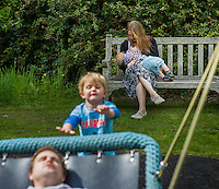 A mother  breastfeeding her child during a family outing to a local park and gardens. Her older boy is pushing her husband on a swing.<br /> <br /> 11-06-2015<br /> Hampshire, England, UK<br /> <br /> © Paul Carter / wdiip.co.uk