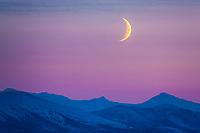 Crescent moon hangs over the Brooks Range mountains, Arctic, Alaska.