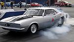 Drag Races. Smoking tires of a silver Camero.