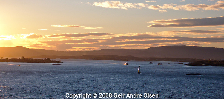 Oslo harbor at sundown with lots of boats going in and out of the harbor.