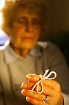 hand of elderly woman with string tied on index finger as reminder